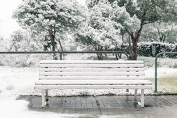 Empty wooden bench covered with snow placed on asphalt walkway in park in winter