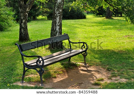 Empty wooden bench in the city park - stock photo