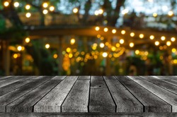 empty wooden board, table or modern wooden terrace with abstract night light bokeh of restaurant at night festival in garden, copy space for display product or object presentation, vintage color tone