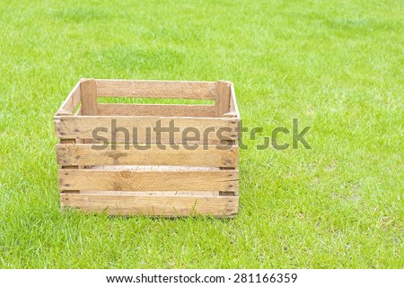 Empty wooden box on green grass, space for text.