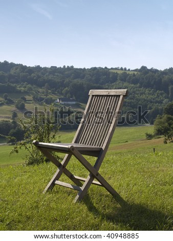 empty wooden chair standing in green grass surrounded by beautiful nature.