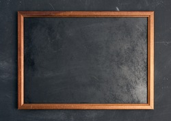 empty wooden chalk board on a black background, place for an inscription