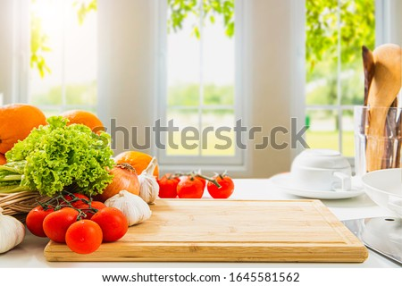 empty wooden chopping board with fresh vegetables and spices, cook on a blurred background, morning kitchen window / area for you to edit products
