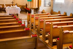 Empty wooden church benches of a Christian church with bible or choir books with cross . Blurry alter in the background. Selective focus. Concept of church service or empty churches.