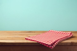 Empty wooden deck table and red checked tablecloth over mint wallpaper background
