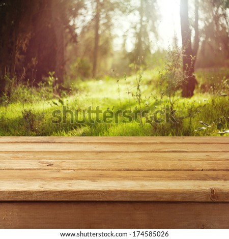 Empty wooden deck table over forest background. Ready for product montage display