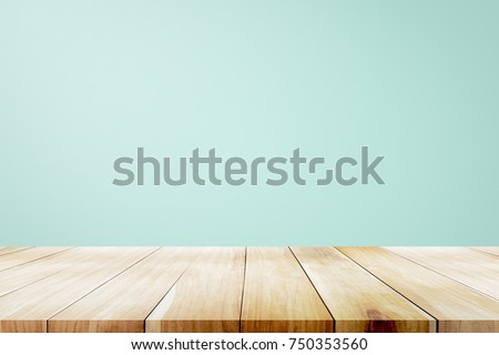 Empty wooden deck table over mint wallpaper background for present product.
