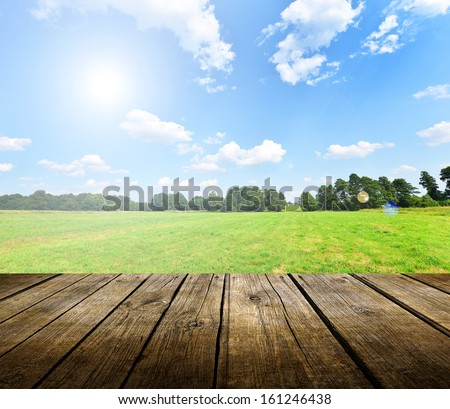 Stock Photo Empty wooden deck table with blue sky in background. Ready for product display montage.