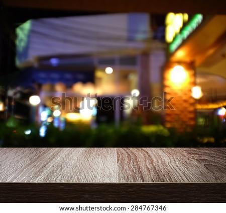 Empty wooden deck table with blur shot night restaurant
