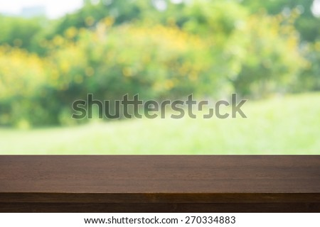 Empty wooden deck table with blured yellow plant background, for product display montage
