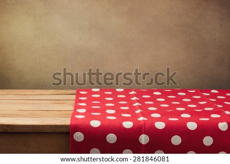 Empty wooden deck table with polka dots tablecloth over grunge background