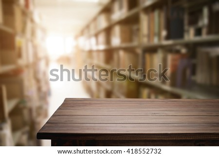 Empty wooden desk space platform with library background for product display.