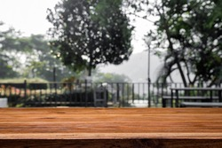 Empty wooden desk with blurred background of park or scenic look out.