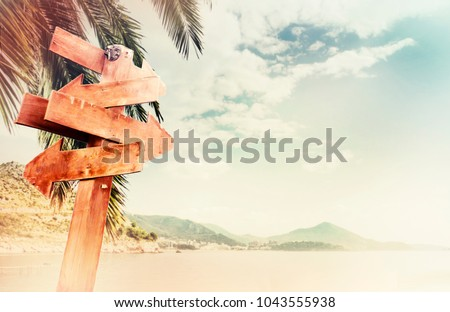 Empty wooden direction sign at the tranquil beach #1043555938