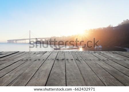 empty wooden floor near golden gate bridge at sunrise