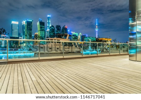 Empty wooden footpath front of shanghai skyline at night