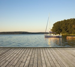Empty wooden jetty on the lake shore with a yacht moored by a jetty in the background
