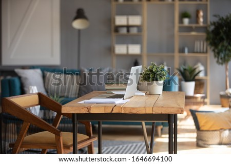 Empty wooden loft desk with open modern laptop and book on, cozy living room interior design of student or freelance employee, comfortable domestic workplace with table and computer in apartment