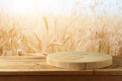 Empty wooden log on rustic table over wheat field background.  Jewish holiday Shavuot mock up for design and product display.