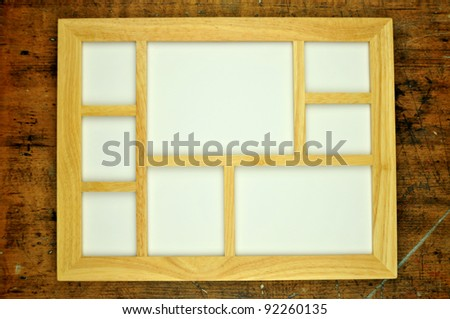 Empty wooden picture frame, on rustic wooden background
