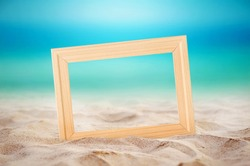 Empty wooden picture frame on the beach sand, summer concept.