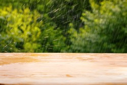 Empty wooden plank table against summer rain and bright green defocused foliage. Background for product or object montage template