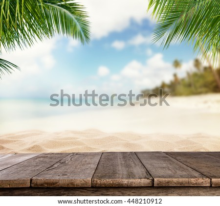 Shutterstock Empty wooden planks with blur beach on background, can be used for product placement, palm leaves on foreground