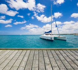 Empty wooden platform with luxury yacht anchored on turquoise water of Caribbean Sea in the background, Dominican Republic