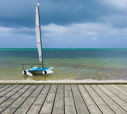 Empty wooden platform with sailboat moored at shore of tropical Bavaro beach in Sargasso sea against dark cloudy sky, Dominican Republic