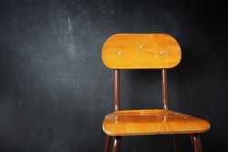 Empty wooden school chair against a black chalkboard in school