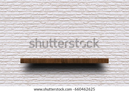 Empty wooden shelf on old white brick wall texture. For display or montage your products with focus wooden shelf top in the foreground. Empty wooden brown shelf. shelves