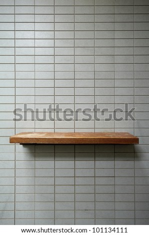 Empty wooden shelf on the tile wall.