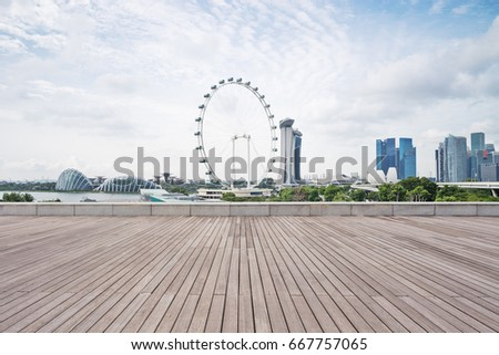 empty wooden sidewalk with modern buildings near ferris wheel