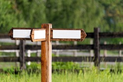 Empty wooden sign with arrows on the ranch. Simple wooden triple direction arrow roadsign in the gargen with wooden fence