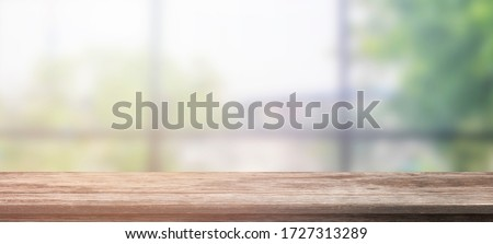 Empty wooden table and blur glass wall background window room interior decoration background, product montage display,can be used for display or montage your products.