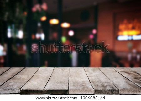 Empty wooden table and blurred background of abstract in front of restaurant or coffee shop for display of product or for montage. #1006088164
