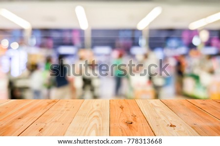 empty wooden table and blurred image of people at the cashier counters in the supermarket #778313668