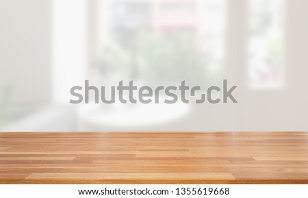 Empty wooden table and blurred modern white kitchen coffee cafe background, restaurants. Ready for product montage #1355619668