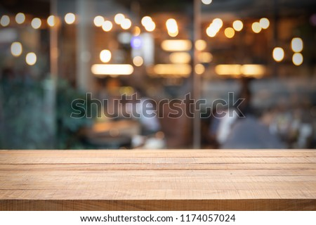 Empty wooden table and blurred restaurant or cafe. Abstract bokeh light. Background concept. Using for Mock up template for display of your design,Banner for advertise of product. #1174057024
