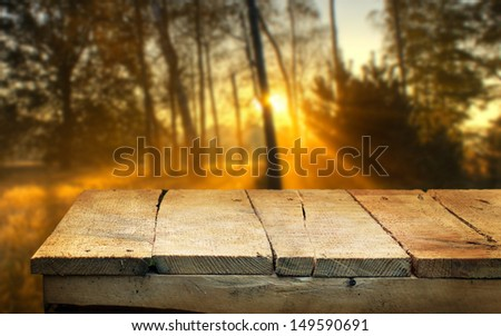 Empty wooden table and defocused autumn dawn in background. Great for product display montages