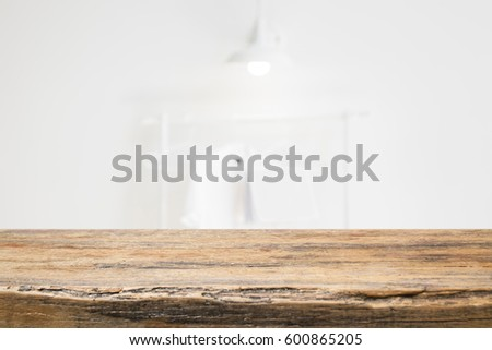 Empty wooden table and modern white clean room background with shirt hanging, lamp, book,  Ready for product montage #600865205