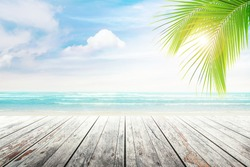 Empty wooden table and palm leaves with party on beach blurred background in summer time.