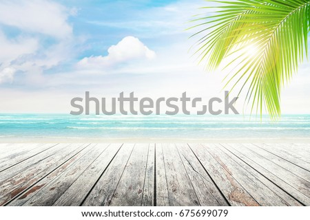 Empty wooden table and palm leaves with party on beach blurred background in summer time. #675699079