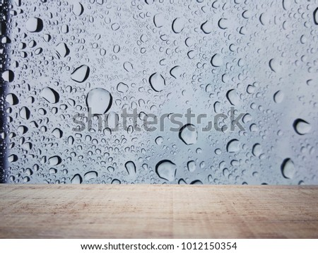 Empty wooden table and raindrop background  with space.Empty for product  display. Ready for product display montage. Fair in blurred and de-focus, Soft focus,Select focus #1012150354