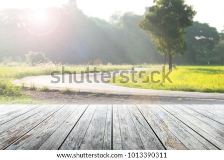 Empty wooden table blurred view the countryside road and sunlight background. #1013390311