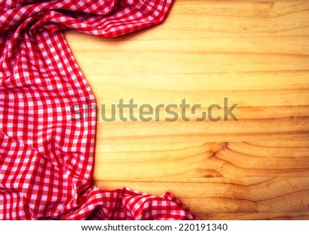 Empty wooden table covered with red checked tablecloth.