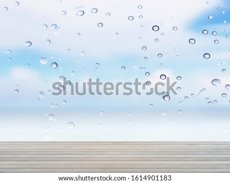 Empty wooden table for displaying products. Wooden table for displaying products. The background is clear glass windows with rain drops. And see the sky. (with copy space)