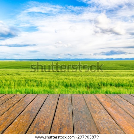 Empty wooden table for product presentation. In the background blurred wheat field  #297905879