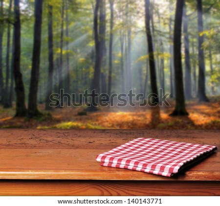 Empty wooden table in  autumn forest. Great background for product display.