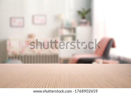 Empty wooden table in baby room interior